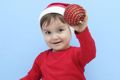 Profile of a little  kid dressed as santa claus with a red bauble in his hand Royalty Free Stock Images