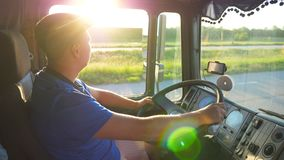 Profile of lorry driver riding through countryside at sunset time. Man in hat controlling his truck and enjoying journey stock footage