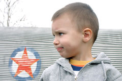 Profile of lour boy. In gray jacket with red star royalty free stock photography