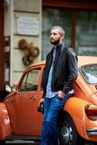 Profile of man leaning on orange retro car. Close-up Stock Photos