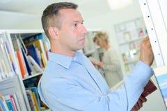 Profile man choosing book off shelf Royalty Free Stock Photos