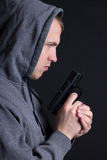 Profile of man criminal with gun over grey Stock Photography