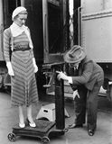 Profile of a man measuring weight of a woman standing on a weighing scale in front of a train Royalty Free Stock Images