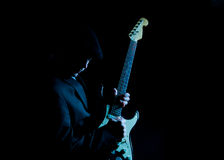 Profile Man playing guitar. Man wearing a black hat , playing guitar on a black background Stock Images
