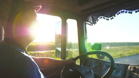 Profile of man riding through countryside with beautiful sunset at background. Lorry driver controlling his truck stock footage