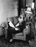 Profile of a man sitting in an armchair and reading a book Royalty Free Stock Image