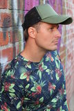 Profile of Man Wearing Shirt with Floral Pattern and Baseball Cap.  Royalty Free Stock Images