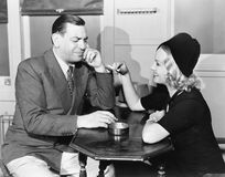 Profile of a man with a young woman smoking sitting in a cafe Stock Image