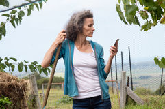 Profile of mature woman with rake and phone Royalty Free Stock Image