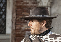 Profile of a Mercenary. Venice, Italy-February 18, 2012:Environmental portrait of a person with a six-shooter disguised as an old time western mercenary posing Royalty Free Stock Photos