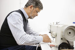 Profile of middle aged tailor using sewing machine Royalty Free Stock Photography