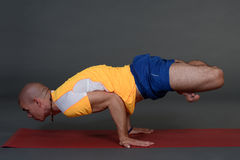 Profile of muscular handsome young healthy man working out, doing yoga excercise. Royalty Free Stock Photography