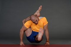 Profile of muscular handsome young healthy man working out, doing yoga excercise. Stock Photos