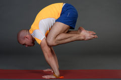 Profile of muscular handsome young healthy man working out, doing yoga excercise. Stock Photography