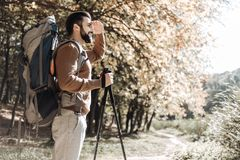 Profile of optimistic traveller enjoying the dawn. Sunny morning. Profile of bearded optimistic traveller touching his forehead while caring rucksack behind his Stock Photography