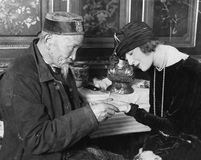 Profile of a palmist reading a palm of a young woman. (All persons depicted are no longer living and no estate exists. Supplier grants that there will be no stock photography