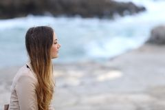 Profile of a pensive woman on the beach in winter. Profile of a serious pensive woman on the beach in winter looking away Royalty Free Stock Photography