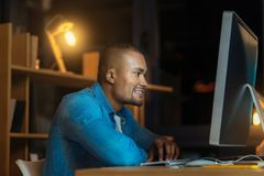 Profile photo of concentrated male while working. Any problem. Positive delighted mulatto keeping smile on his face and putting elbows on the table while doing Stock Photo