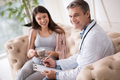 Profile photo of delighted medical worker that looking at camera. Good news. Handsome gynecologist keeping smile on his face and sitting near his patient while royalty free stock images