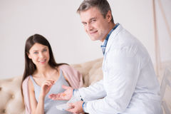 Profile photo of medical worker that giving tablet. Try to be serious. Delighted doctor keeping smile on his face and sitting in semi position while looking at royalty free stock photo