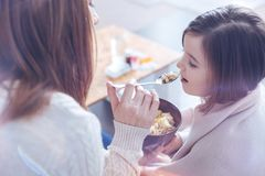 Profile photo of mother that giving dinner to her daughter stock images
