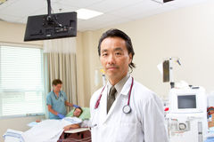 Profile of physician in renal unit. Profile of physician with patient and nurse in background Stock Photos