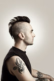 Profile. Picture of a tattooed man with mohawk style hair Stock Photos