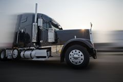 Profile of dark bonnet classic big rig semi truck going on the r. Profile of popular American dark bonnet classic big rig semi truck tractor with chrome and royalty free stock photo