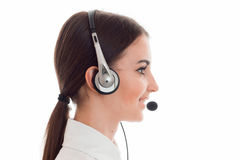 Profile portrait of attractive brunette call center worker girl with headphones and microphone isolated on white Royalty Free Stock Photo