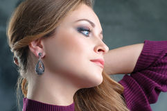 Profile portrait of beautiful woman wearing ethnic silver earrin royalty free stock image