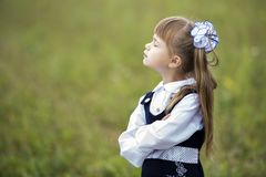 Profile portrait of cute adorable first grader girl in school uniform and white bows in long hair with raised head and closed eyes. On blurred green sunny light stock photos
