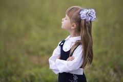 Profile portrait of cute adorable first grader girl in school uniform and white bows in long hair with raised head and closed eyes. On blurred green sunny light royalty free stock image