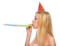 Profile portrait of girl in cap blowing in party horn blower Royalty Free Stock Image