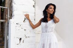 Profile portrait of a bride in a white wedding dress, touching her hair lightly, poses near a white wall, looking away. royalty free stock photos