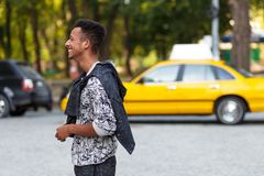 Profile portrait of a mixed race young man in casual clothes standing outside,  on a street blurred background. stock photos