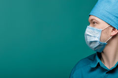 Profile portrait of male surgeon in mask on blue background, close up. copy space Stock Image