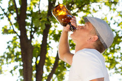 Profile portrait of a man drinking from a bottle Stock Photos