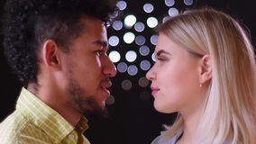 Profile portrait of multinational couple watching passionately and smilingly into eyes on blurred lights background. stock video