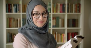 Profile portrait of muslim student in hijab and glasses reading book attentively smiles into camera at the library. stock video footage