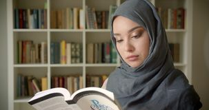 Profile portrait of muslim student in hijab reading book attentively smiles into camera at the library. stock video footage