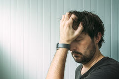 Profile portrait od miserable troubled man. With serious expression, depressive male with hand on face royalty free stock image