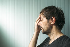 Profile portrait od miserable troubled man. With serious expression, depressive male with hand on face royalty free stock images