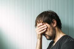 Profile portrait od miserable troubled man. With serious expression, depressive male with hand on face stock photo