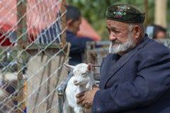 Profile portrait of old man with young goat, Sunday Livestock Ma. Kashgar, Xinjiang, China - September 16, 2018 : Profile portrit of old Uyghur man with young royalty free stock photography