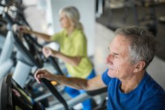 Senior man working out on stair stepper at gym. Profile portrait of senior men working out on stair stepper at gym Royalty Free Stock Image