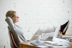 Profile portrait of student girl, legs on desk, arms behind Royalty Free Stock Photo