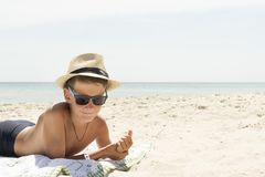 Portrait of hipster relaxing boy in hat and glasses on beach. Profile portrait of teenager boy in hat on beach Royalty Free Stock Image