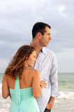 Profile portrait of well dressed young couple look. A well dressed young couple  with their bodies facing each other, both are looking out at the ocean to the Stock Photography