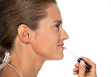 Profile portrait of woman applying lip gloss Royalty Free Stock Photo