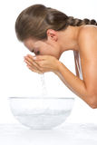 Profile portrait of woman washing face in glass bowl with water Royalty Free Stock Photography